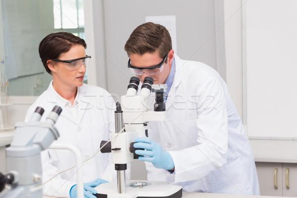 Regarder microscope laboratoire femme technologie Photo stock © wavebreak_media