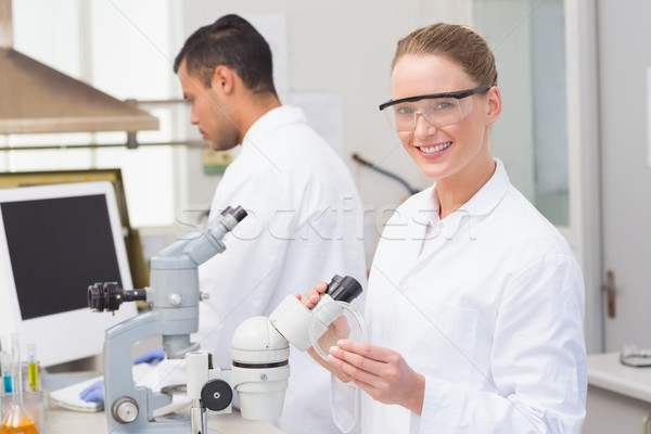Scientist examining petri dish smiling at camera  Stock photo © wavebreak_media