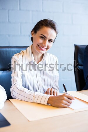 Businesswoman having phone call and looking at documents  Stock photo © wavebreak_media