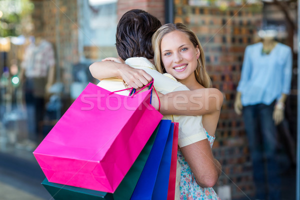 Smiling woman with shopping bags hugging her boyfriend Stock photo © wavebreak_media