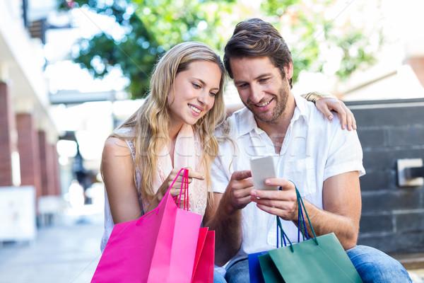 Mosolyog pár bevásárlótáskák ül okostelefon pláza Stock fotó © wavebreak_media