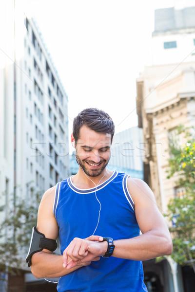 Smiling handsome athlete setting heart rate watch Stock photo © wavebreak_media