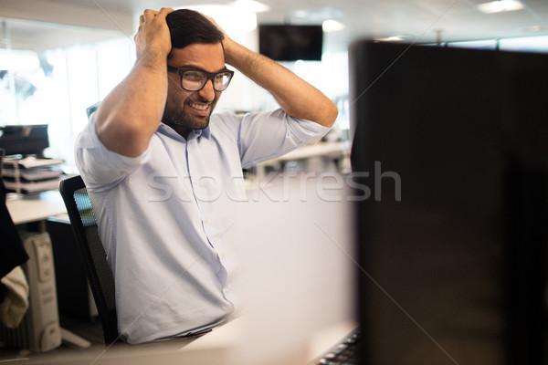 Tensed businessman clenching teeth in office Stock photo © wavebreak_media