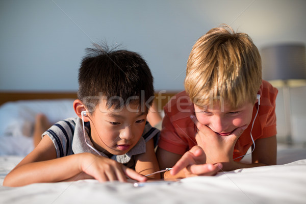 Siblings listening to music while using mobile phone on bed Stock photo © wavebreak_media