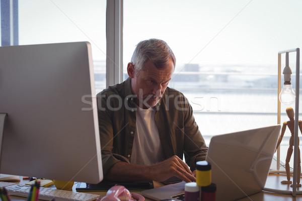 Sério empresário trabalhando laptop mesa de escritório criador Foto stock © wavebreak_media