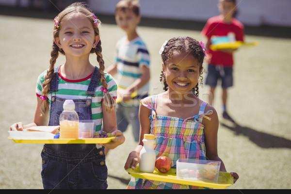 Portrait of happy schoolgirls holding meal in tray Stock photo © wavebreak_media
