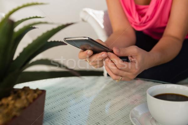 Középső rész nő mobiltelefon kávézó ül asztal Stock fotó © wavebreak_media