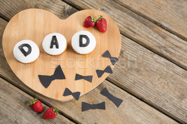 Cupcakes with strawberries on wooden cutting board Stock photo © wavebreak_media