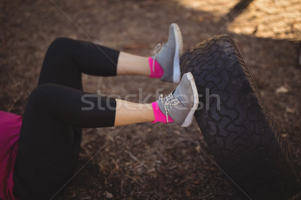 Low section of woman exercising with huge tyre during obstacle course Stock photo © wavebreak_media