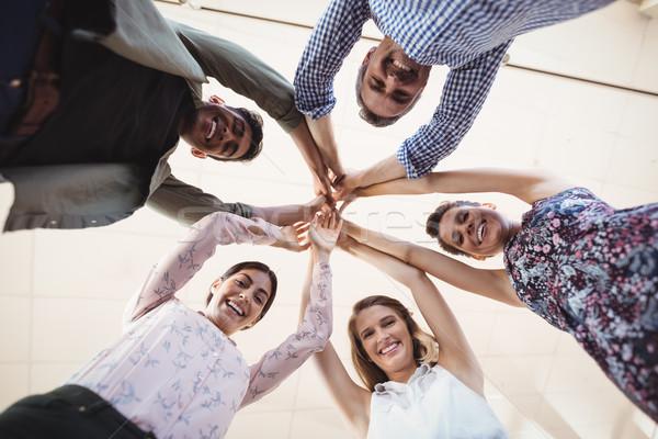 Directly below portrait of smiling business people raising hands together Stock photo © wavebreak_media