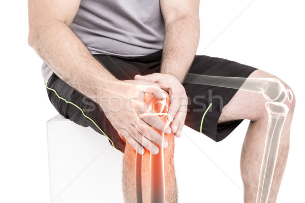 Man suffering with knee pain while sitting against white background Stock photo © wavebreak_media