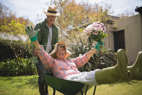 Man carrying cheerful senior woman holding bouquet in wheel borrow Stock photo © wavebreak_media