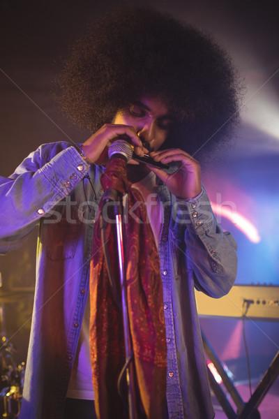 Masculina músico jugando boca órgano iluminado Foto stock © wavebreak_media