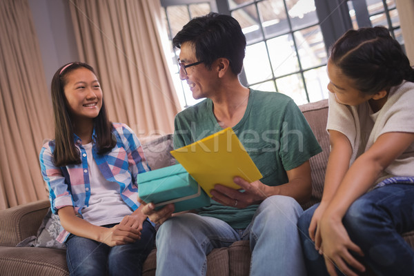 Father receiving greeting card and gift box from siblings in living room Stock photo © wavebreak_media