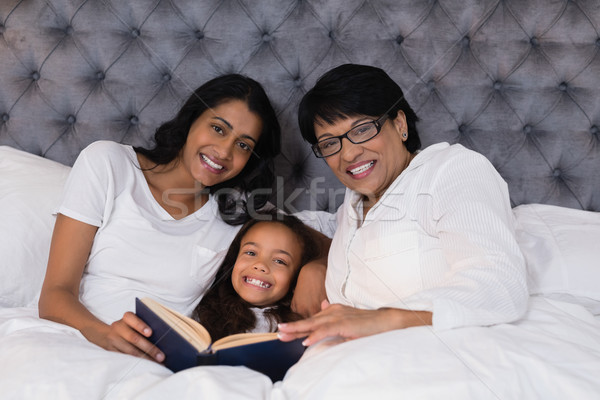 Portrait of smiling multi-generation family with book resting on bed Stock photo © wavebreak_media