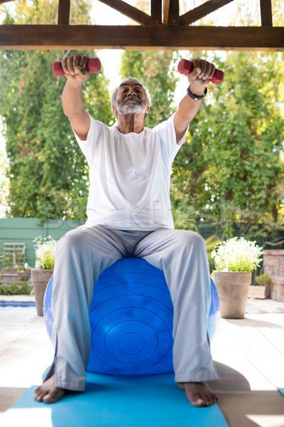 Full length of man exercising while sitting on fitness ball Stock photo © wavebreak_media