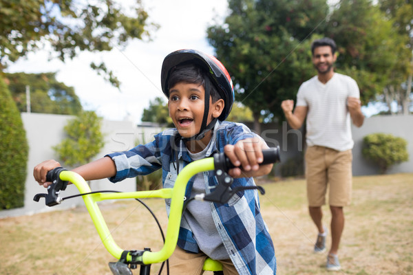 Stock photo: Boy cycling with father standing in background