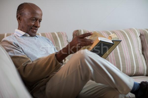 Uśmiechnięty starszy człowiek czytania książki domu Zdjęcia stock © wavebreak_media