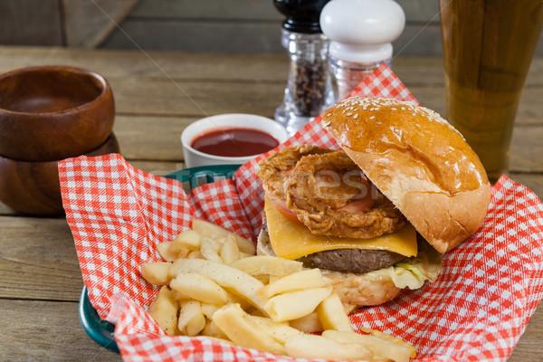 Burger frites françaises osier panier table en bois bière Photo stock © wavebreak_media