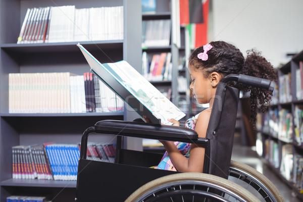Girl reading book on wheelchair Stock photo © wavebreak_media