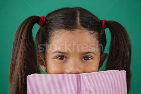школьница сокрытие за книга зеленый портрет Сток-фото © wavebreak_media
