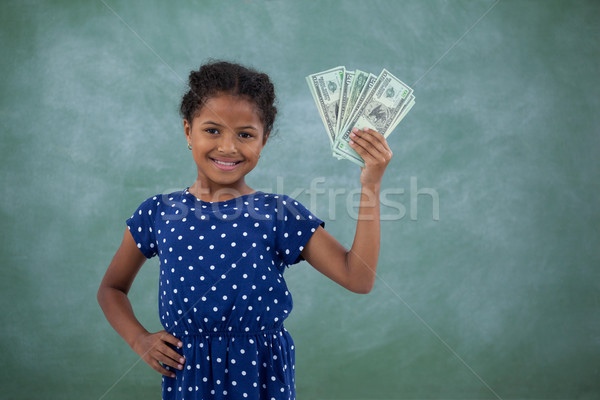 Smiling girl with hand on hip showing paper currency Stock photo © wavebreak_media