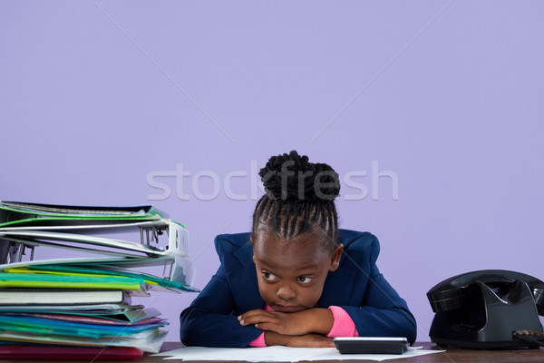 Bored businesswoman leaning by files and telephone on desk Stock photo © wavebreak_media