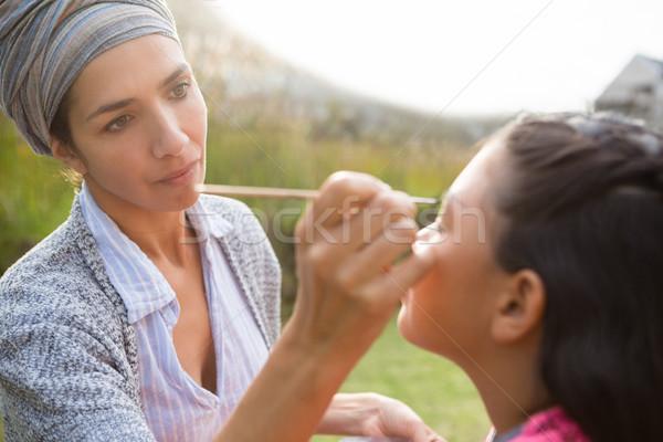 Young woman applying face paint Stock photo © wavebreak_media