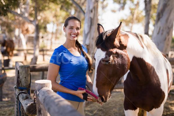 Retrato feminino jóquei limpeza cavalo em pé Foto stock © wavebreak_media