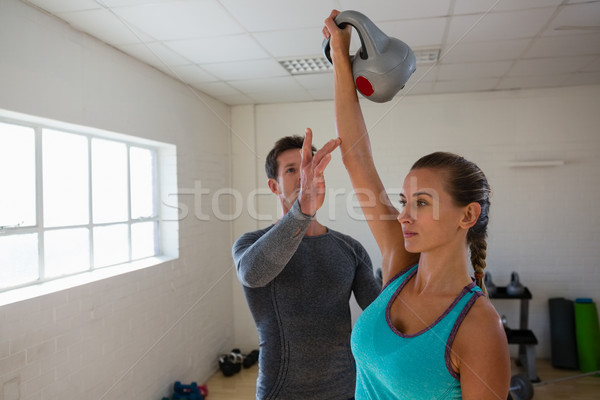 Male trainer assisting female athlete in lifting kettlebells Stock photo © wavebreak_media