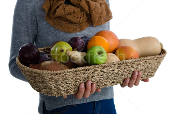 Mid section of woman carrying vegetables and fruits in wicker basket while standing against white ba Stock photo © wavebreak_media