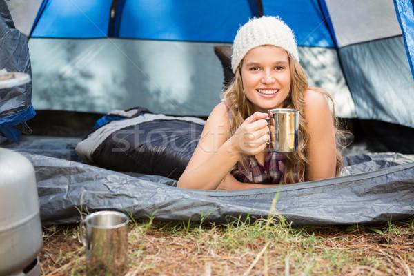 Pretty blonde camper smiling and lying in tent Stock photo © wavebreak_media