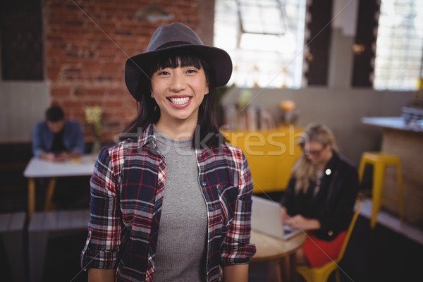 Smiling young woman wearing hat standing at coffee shop Stock photo © wavebreak_media