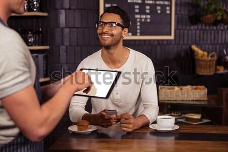 Smiling male professional holding fresh burger at coffee shop Stock photo © wavebreak_media