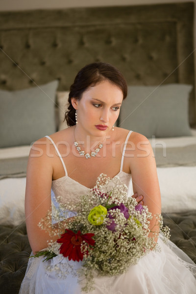Sad bride with bouquet sitting on bed Stock photo © wavebreak_media