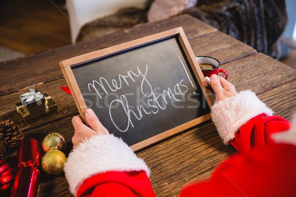 Santa Claus holding a slate with merry christmas text Stock photo © wavebreak_media