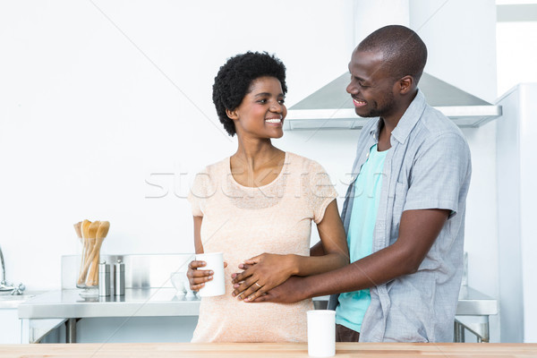 Pregnant couple embracing while having cup of coffee Stock photo © wavebreak_media