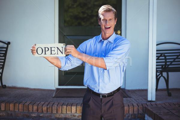 Handsome businessman holding an open sign Stock photo © wavebreak_media