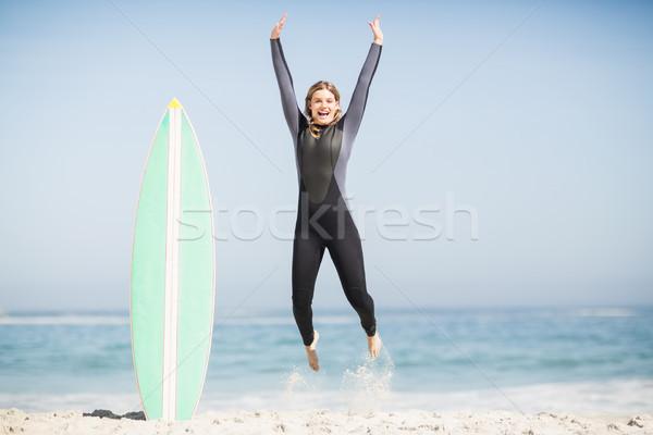 Izgatott nő ugrik szörfdeszka tengerpart tenger Stock fotó © wavebreak_media