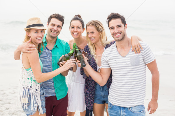 Group of friends toasting beer bottles on the beach Stock photo © wavebreak_media