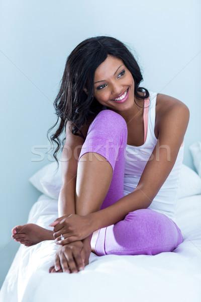 Nadenkend vrouw vergadering bed glimlachend slaapkamer Stockfoto © wavebreak_media
