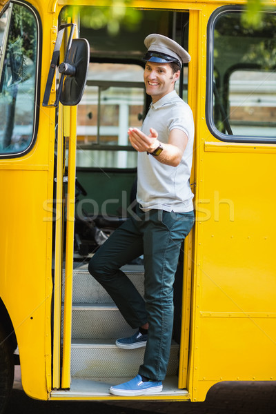 Bus driver standing at the entrance of bus and gesturing Stock photo © wavebreak_media