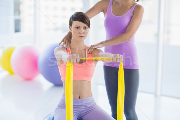 Woman with trainer holding resistance band Stock photo © wavebreak_media