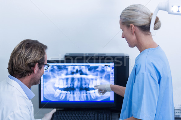 Dentist and dental assistant discussing a x-ray on the monitor Stock photo © wavebreak_media