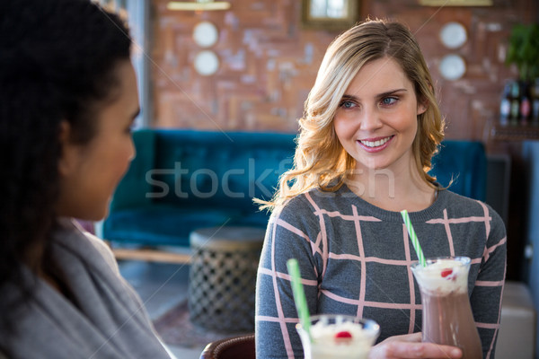 Female friends interacting with each other while having coffee Stock photo © wavebreak_media
