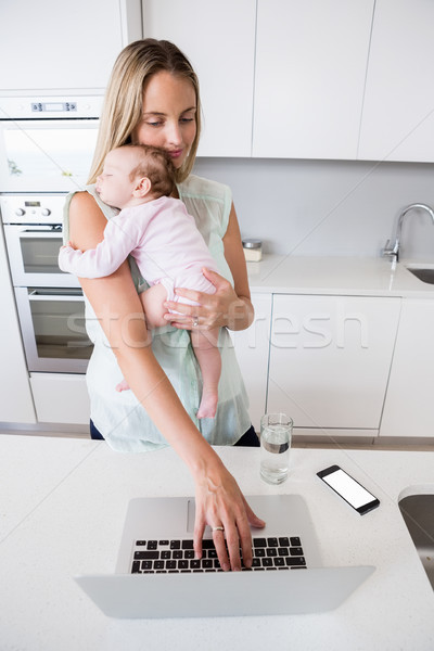 Moeder met behulp van laptop baby keuken home Stockfoto © wavebreak_media