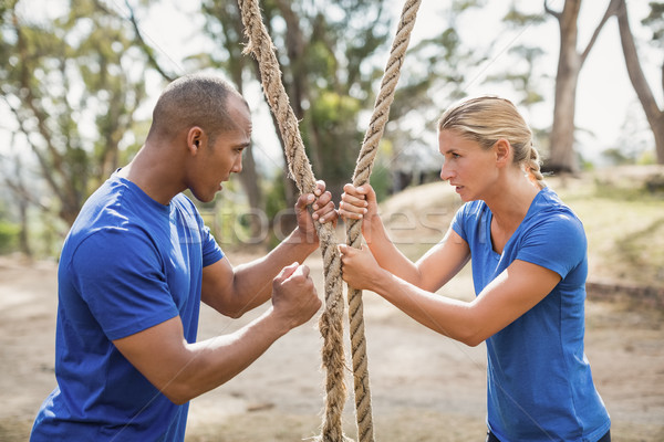 Male trainer assisting woman in rope climbing during obstacle course Stock photo © wavebreak_media