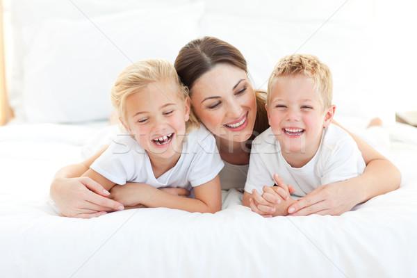 Boldog testvérek játszik anya ágy otthon Stock fotó © wavebreak_media