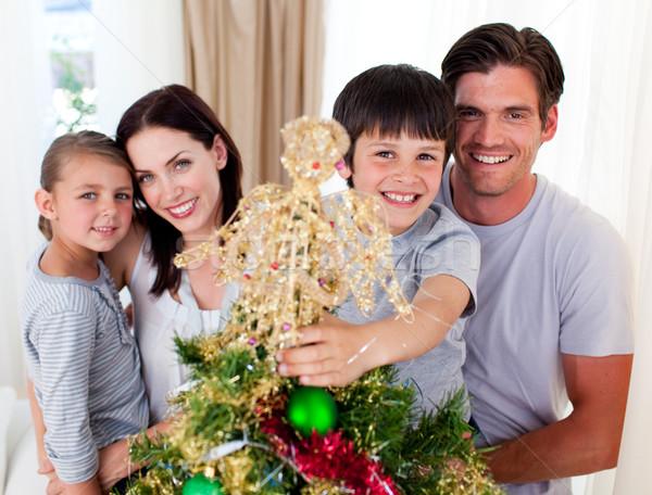Portrait of a family decorating a Christmas tree Stock photo © wavebreak_media