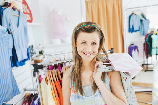 Stock photo: Beautiful blond woman holding shopping bags smiling at the camera in a clothes store